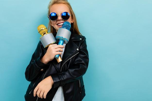 Het kaukasische tienermeisje met bruin haar in zwarte jas, blauwe zonnebril zingt liedjes met blauwe en gele microfoons die op blauwe achtergrond worden geïsoleerd