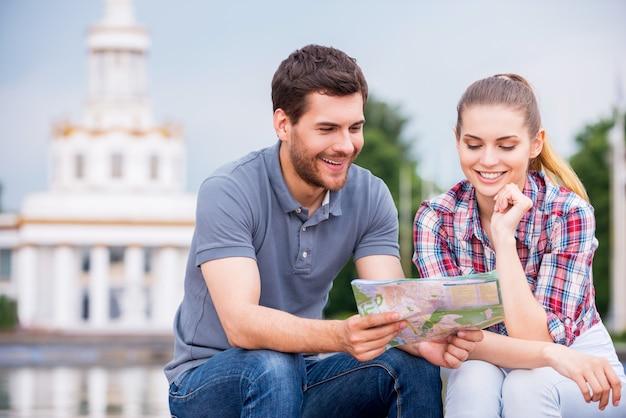 Het kiezen van de plek om naartoe te gaan. gelukkig jong toeristenpaar dat dichtbij mooi gebouw zit en kaart samen onderzoekt