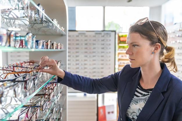 Het kiezen van een bril in de optiekwinkel door een jonge vrouw
