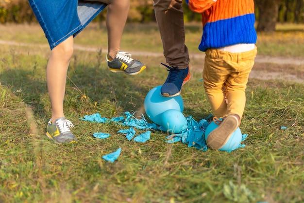 Het kind barst ballonnen met plezier tijdens het wandelen met zijn ouders.