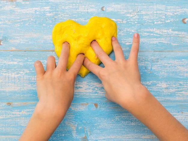 Het kind beeldhouwt een hart van geel slijm op een blauwe tafel. antistress voor speelgoed. speelgoed voor de ontwikkeling van handmotoriek.