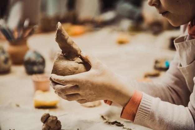 Het kind beeldhouwt het product uit ruwe klei