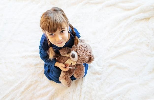 Het kind behandelt een beer. het spel van de dokter. selectieve aandacht.