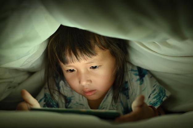 Het kind bekijkt video slimme telefoon onder de deken op bed 's nachts lichtflitsen weerspiegeld van het scherm, kinderen die spelen met verslaving en cartoon concept