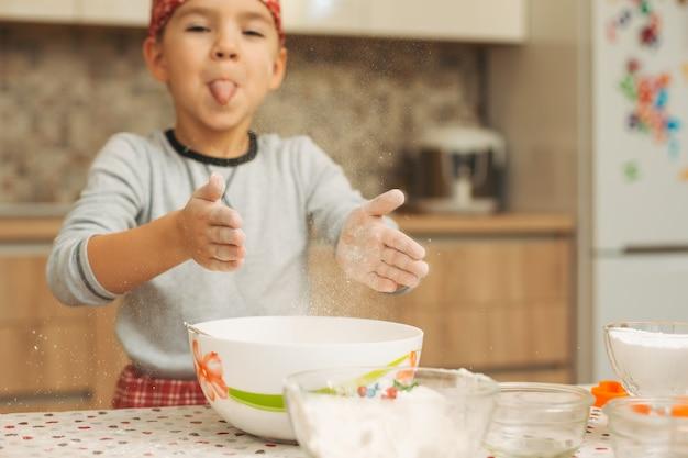 Het kind bereidt het deeg voor, bakt koekjes in de keuken
