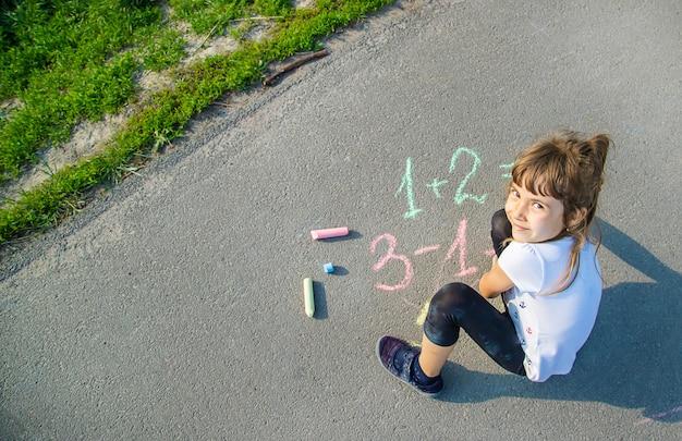 Het kind beslist grommend op het asfalt