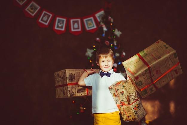 Het kind bevindt zich met een huidige doos vóór een kerstboom