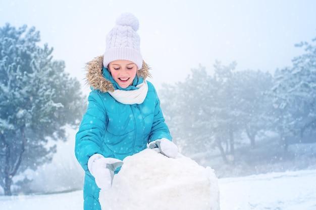 Het kind bouwt een sneeuwpop. meisje in de sneeuw. winterpret.