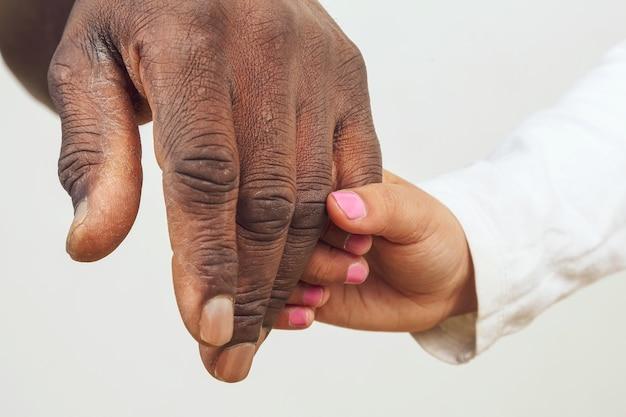 Het kind dat de hand vasthoudt van een vader met een donkere huidskleur. ouder-kind relatie. intimiteit en vertrouwen.