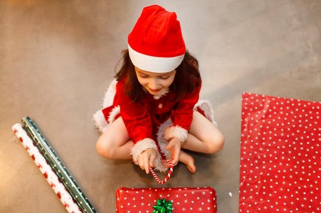 Het kind dat met kerstmis wordt omringd stelt thuis voor