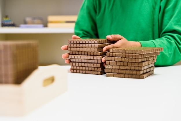 Het kind dat sommige blokken plaatst om aantallen te tellen is zijn huis