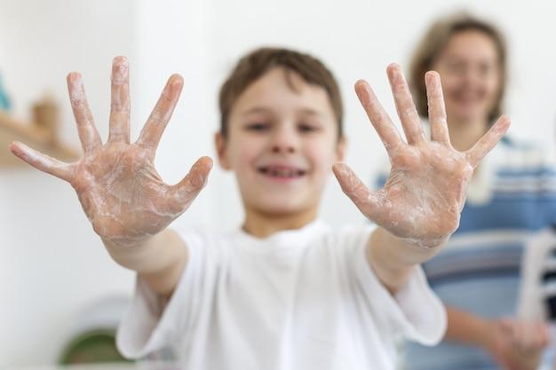 Het kind dat van smiley zeepachtige handen toont