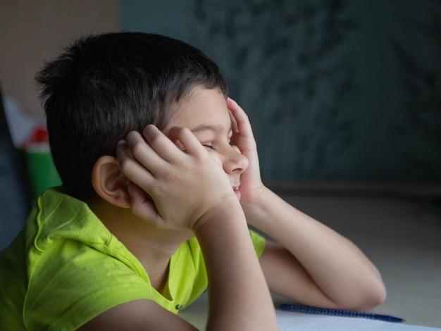 Het kind, de schooljongen, wil geen moeilijk huiswerk maken, zit verveeld aan tafel