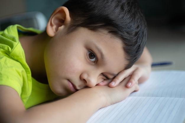 Het kind, de spaanse schooljongen, wil geen moeilijk huiswerk maken, verveeld