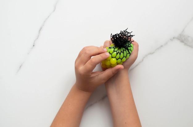Het kind doet een oefening met een reliëfbal voor tactiele sensaties. gemakkelijke zintuiglijke lessen voor kinderen. kleine handen houden een gele stressbal op een witte achtergrond.