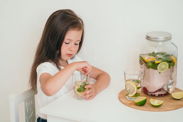 Het kind drinkt een drankje met vitamines. huisgemaakte koude limonade met citroen, limoen en munt. het meisje zit aan tafel en drinkt limonade.