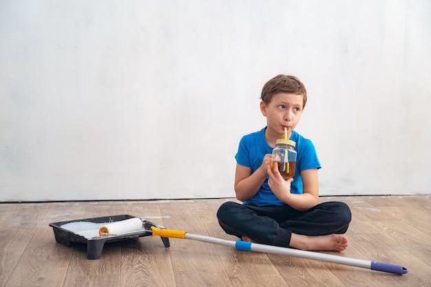 Het kind drinkt thee tijdens de reparatie van de muur.