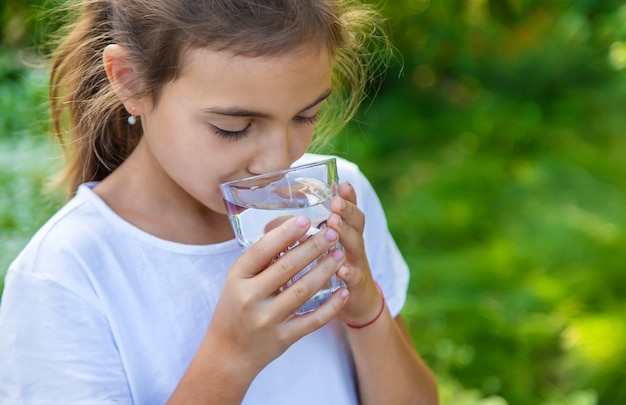 Het kind drinkt water uit een glas. selectieve aandacht. kind.