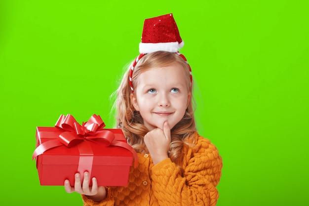 Het kind droomt en houdt een doos met een geschenk vast.