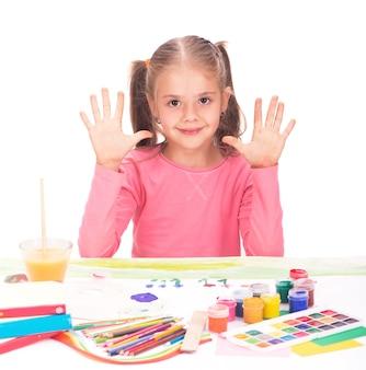 Het kind een klein meisje trekt verven geïsoleerd op een witte achtergrond