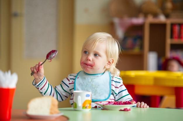 Het kind eet gezond voedsel op de kleuterschool of thuis en wordt vies