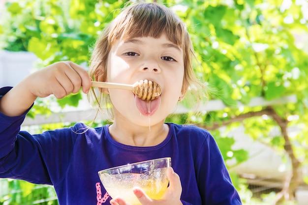 Het kind eet honing. selectieve aandacht. natuur.