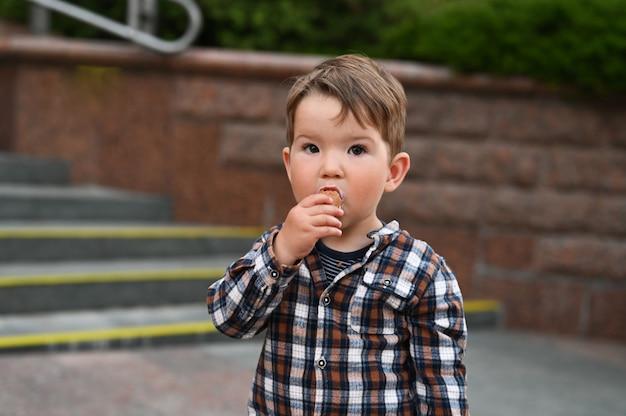 Het kind eet ijs op straat