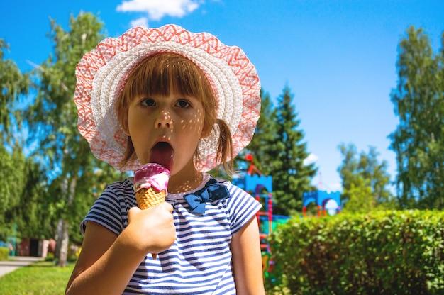 Het kind eet ijs tijdens een wandeling in het park. geluk en vreugde van een klein meisje is zo charmant, haar zomerkleding herinnert aan vrije en gemakkelijke dagen aan familievakanties.