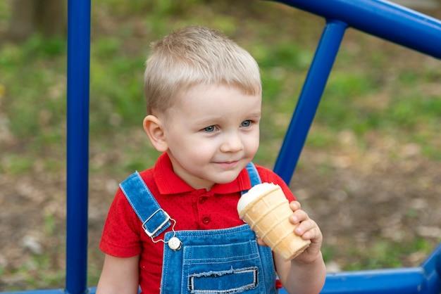 Het kind eet in de zomer ijs op straat