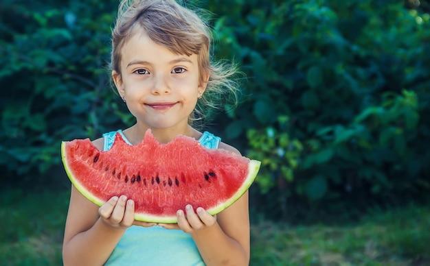 Het kind eet in de zomer watermeloen. selectieve aandacht.