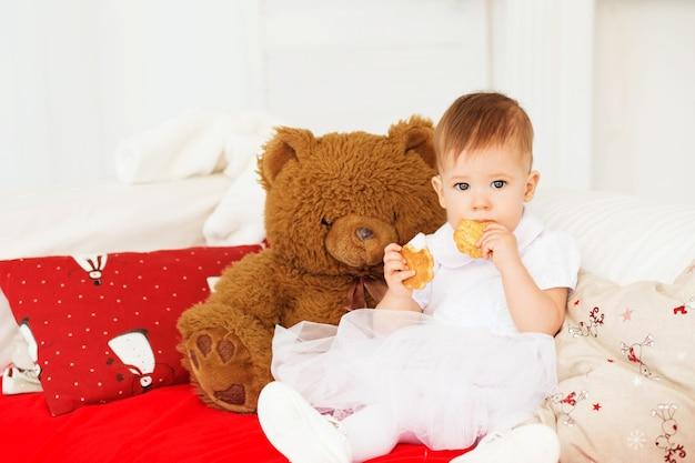 Het kind eet koekjes. portret van een mooi babymeisje met een zachte bruine teddybeer in het interieur met kerstversiering.