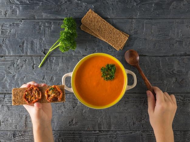 Het kind eet soeppuree van paprika met gedroogde tomaten en toast. soep van het vegetarische dieet. plat leggen. het uitzicht vanaf de top.