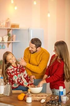 Het kind en haar ouders koken samen in de keuken en voelen zich geweldig