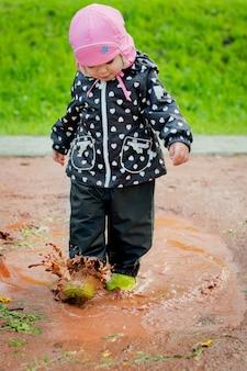 Het kind gaat door de plassen
