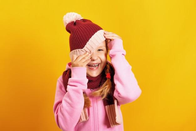Het kind gluurt onder de hoed vandaan.