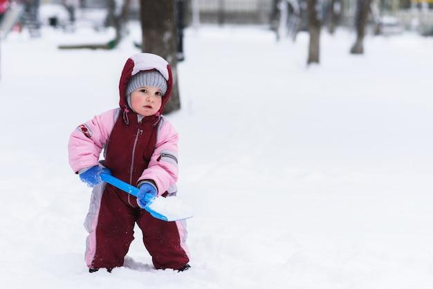 Het kind graaft de sneeuw met een schop