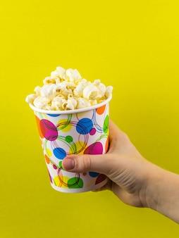 Het kind heeft een veelkleurig glas popcorn op een gele ondergrond.