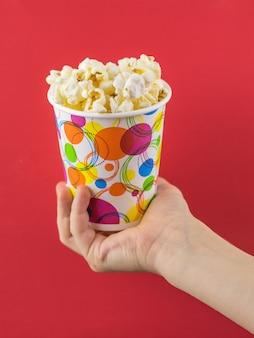 Het kind heeft een veelkleurig glas popcorn op een rode ondergrond
