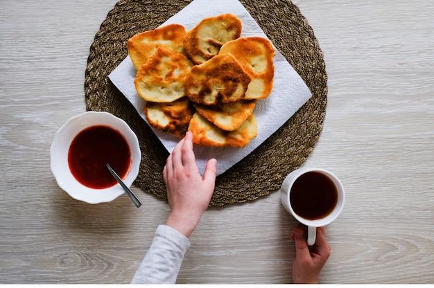 Het kind heeft ontbijt. gebakken aardappelen en jam voor het ontbijt.