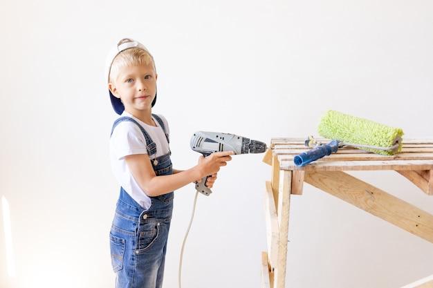 Het kind helpt om thuis reparaties uit te voeren, boort met een boormachine