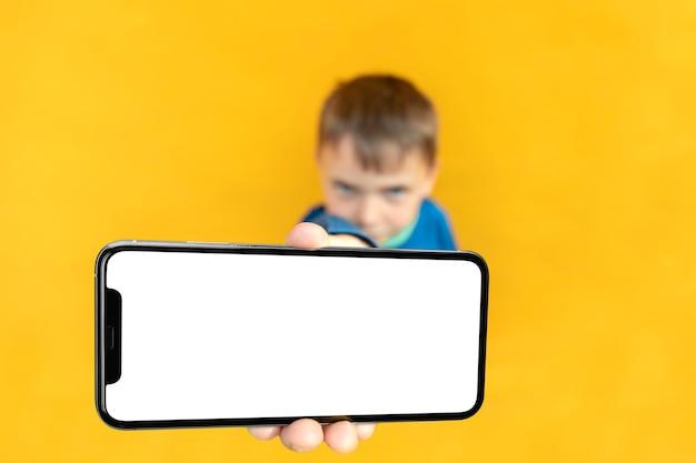 Het kind houdt de telefoon in zijn hand voor reclame op een geel oppervlak. kleur