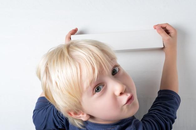 Het kind houdt doos in handen op wit. schattige kleine jongen is blij het pakket. bovenaanzicht