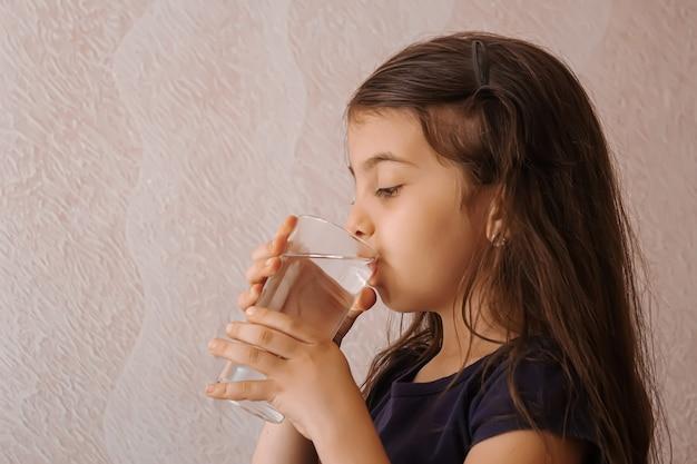 Het kind houdt een glas water in haar handen. selectieve focus.mensen
