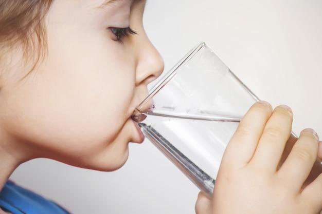 Het kind houdt een glas water in zijn handen. selectieve aandacht.