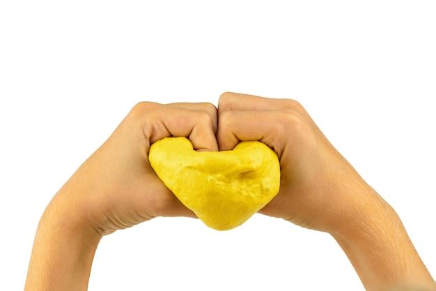 Het kind houdt een hart van geel geïsoleerd slijm vast. antistress voor speelgoed. speelgoed voor de ontwikkeling van handmotoriek.
