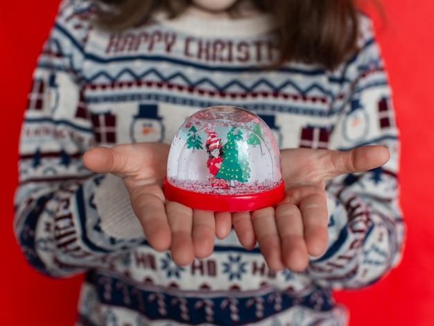 Het kind houdt een kerstbal vast