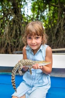 Het kind houdt een kleine krokodil in zijn handen.