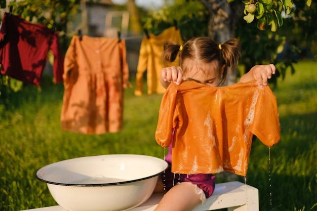 Het kind houdt een shirt nat na het wassen in zijn handen