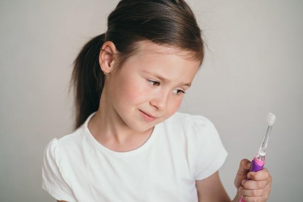 Het kind houdt een tandenborstel in zijn handen kinderen zijn te lui om elke dag hun tanden te poetsen een meisje...