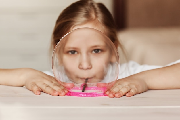 Het kind houdt speelgoed vast dat slijm wordt genoemd, het kind heeft plezier en experimenteert.